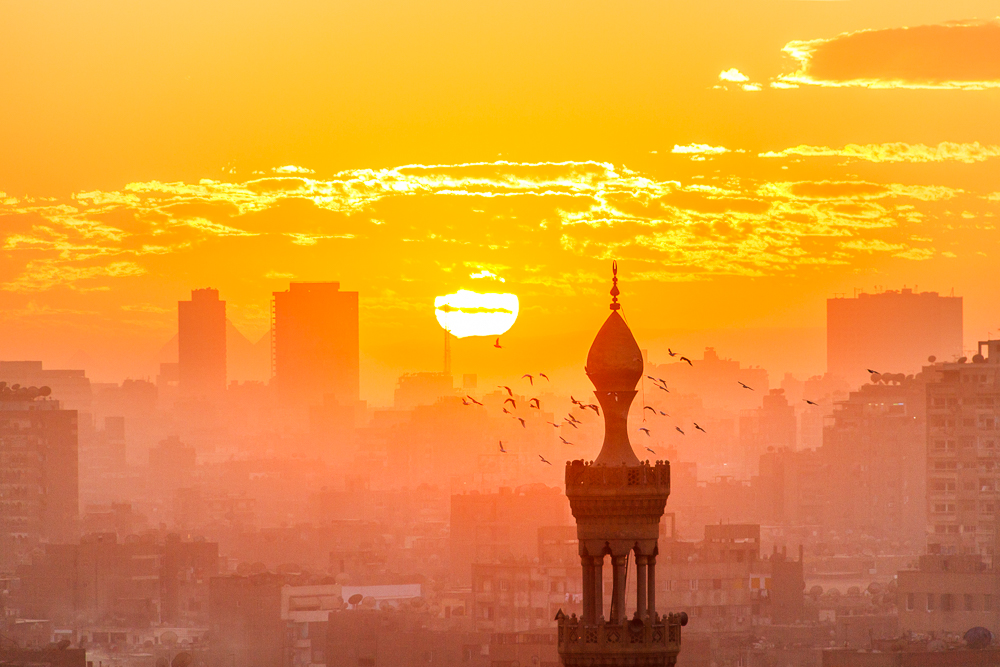 Sunset in Cairo from Al Azhar Garden. In the background, the Pyramids behind the two buildings. Birds around a minaret in the front.